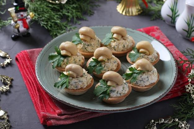Aperitivo em tortinhas com cogumelos, ovo e queijo em um fundo cinza.