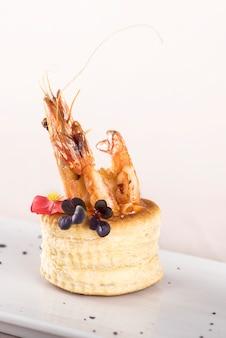 Aperitivo fresco com camarão, na pastelaria, decorado com flor vermelha comestível e folha verde