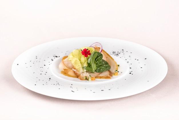 Aperitivo fresco com peixe branco defumado, rúcula, espinafre e salada verde, com flores vermelhas