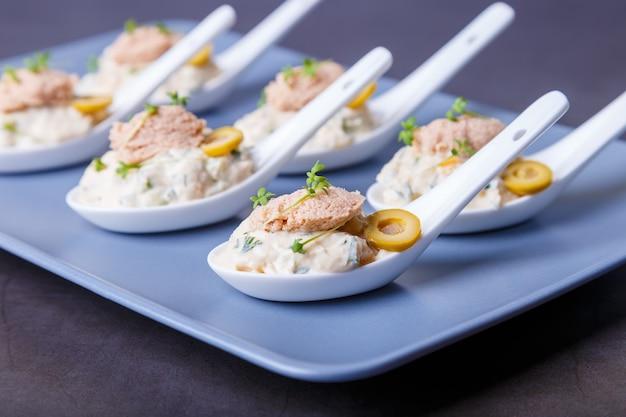 Aperitivo frio à base de fígado de bacalhau, caviar de bacalhau, azeitonas, pepino e microgreens nas colheres de servir. prato frio tradicional. close-up, placa azul, fundo preto.