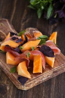 Aperitivo, melão com jamon e manjericão, em um dochk de madeira.