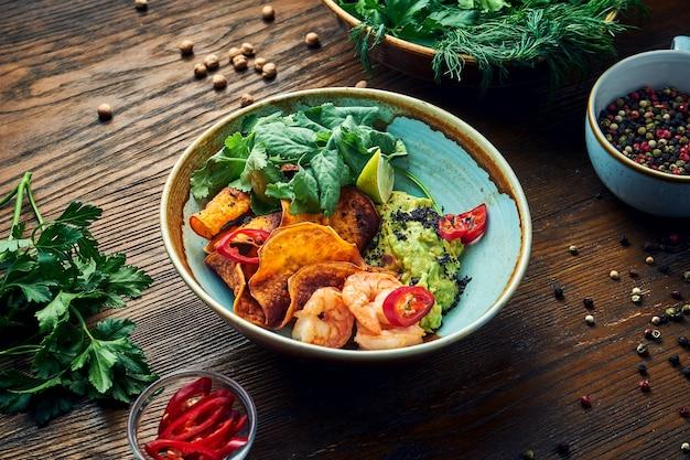 Aperitivo mexicano apetitoso - guacamole de abacate com camarão, batatas fritas de vegetais e coentro em uma tigela sobre uma mesa de madeira. vista de perto
