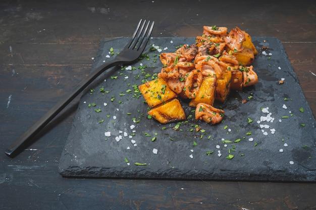 Aperitivo ou lula baby tapa típica espanhola com alho e batatas servidos em um branco alongado