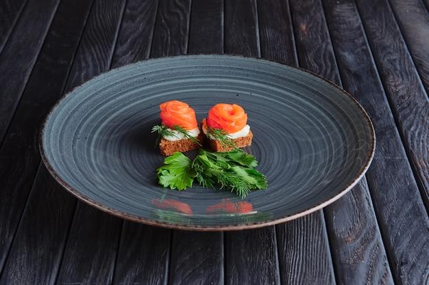 Aperitivo para recepção. salmão defumado com ricota e endro no pedaço de pão integral