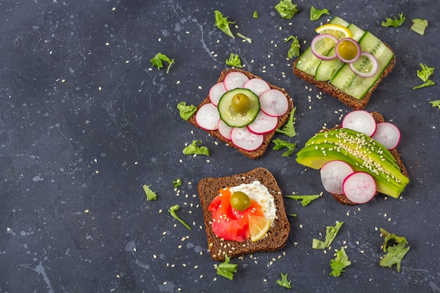 Aperitivo, sanduíche aberto com diferentes coberturas: salmão e vegetais (abacate, pepino, rabanete) em fundo escuro. alimentação saudável