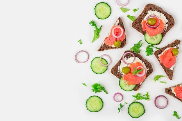 Aperitivo, sanduíche aberto com salmão, cebola e pepino em fundo branco. cozinha tradicional italiana ou escandinava. conceito de nutrição adequada e alimentação saudável
