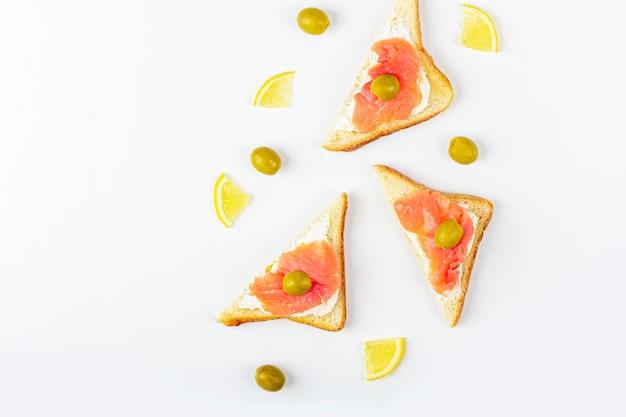 Aperitivo, sanduíche aberto com salmão e queijo no fundo branco. cozinha tradicional italiana ou escandinava. conceito de nutrição adequada e alimentação saudável. postura plana, cópia espaço para texto