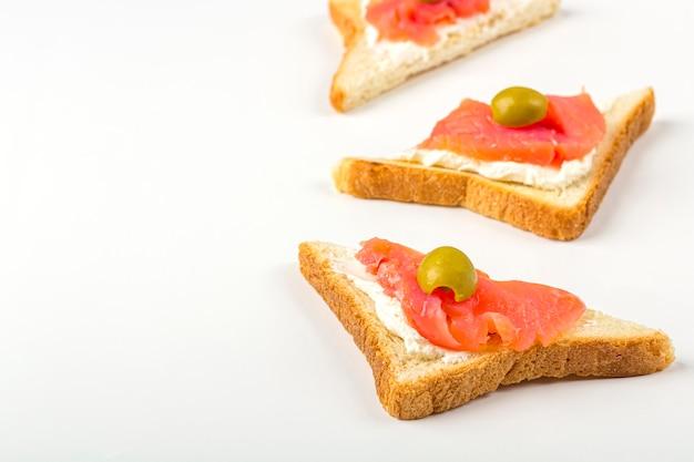Aperitivo, sanduíche aberto com salmão e queijo no fundo branco. cozinha tradicional italiana ou escandinava. conceito de nutrição adequada e alimentação saudável