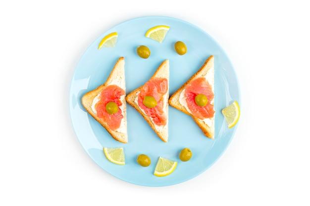 Aperitivo, sanduíche aberto com salmão em um prato azul sobre fundo branco. cozinha tradicional italiana ou escandinava. conceito de nutrição adequada e alimentação saudável