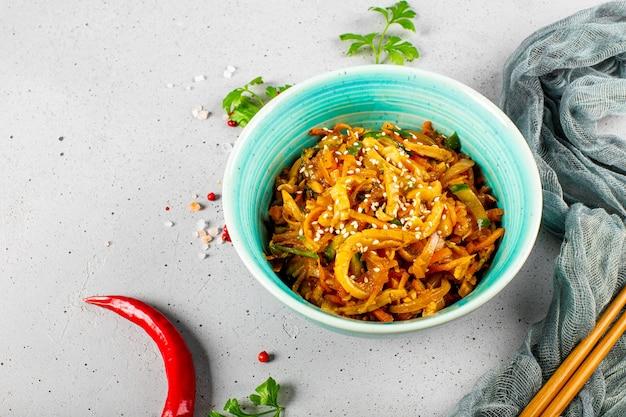 Aperitivo tradicional asiático, ele ou hwe, salada de lula picante com legumes em uma tigela sobre a mesa.