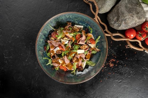 Aperitivo vegetariano frio com rúcula, tomate cereja, filé de frango, ameixa, queijo e tomate seco