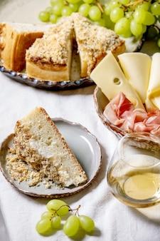 Aperitivos antepastos com focaccia siciliana branca. bolo de pão tradicional fatiado com cebola servido com presunto, queijo, uvas e um copo de vinho branco na toalha de mesa branca.