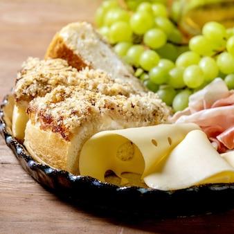 Aperitivos antepastos com focaccia siciliana branca. bolo de pão tradicional fatiado com cebola servido com presunto, queijo, uvas sobre fundo de madeira. fechar-se