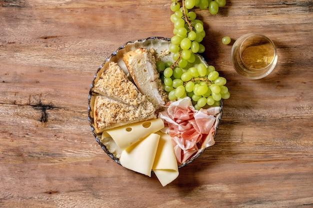 Aperitivos antepastos com focaccia siciliana branca. bolo tradicional de pão fatiado com cebola servido com presunto prosciutto, queijo, uvas e taça de vinho branco