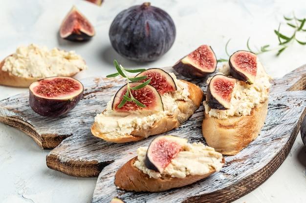 Aperitivos. bruschettas com figos, queijo de pasta mole. delicioso café da manhã ou lanche, comer limpo, fazer dieta, conceito de comida vegan. vista do topo.