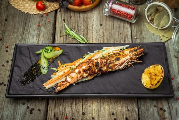 Aperitivos camarão grelhado com rodela de salsa e limão, em mesa de madeira