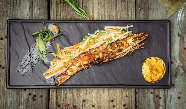 Aperitivos de camarão grelhado com rodela de salsa e limão, sobre fundo de madeira