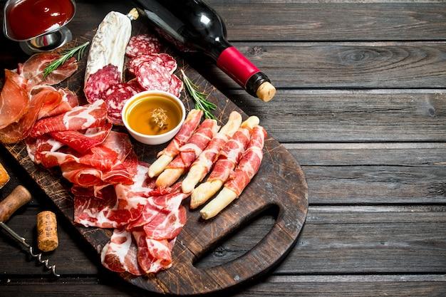 Aperitivos de carne italiana com vinho tinto em uma mesa rústica.