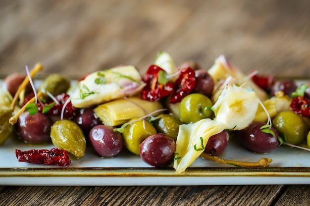 Aperitivos de vinho azeitonas alcachofras e tomates