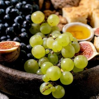 Aperitivos de vinho com diferentes uvas, figos, nozes, pão, mel e queijo de cabra na placa de cerâmica sobre fundo de madeira velho. fechar-se. imagem quadrada