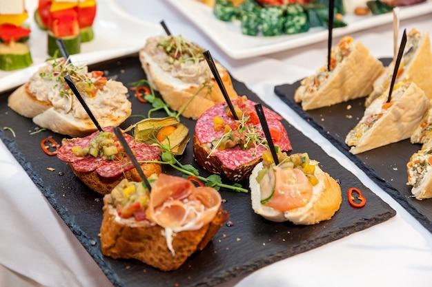 Aperitivos lindamente decorados para a mesa de banquete de catering. refeições para eventos, snacks em buffet