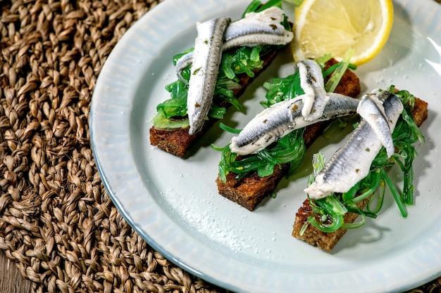 Aperitivos tapas anchovas em conserva ou filé de sardinha salada de algas wakame no pão de centeio torrado