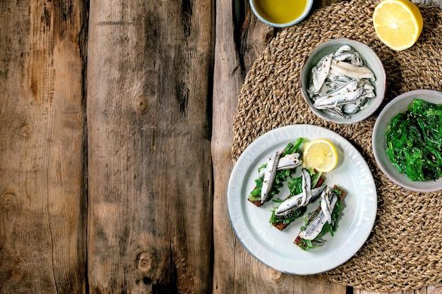 Aperitivos tapas de anchovas em conserva ou filé de sardinha salada de algas wakame em pão de centeio torrado, servido em prato azul com limão. postura plana, copie o espaço.