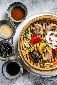 Aperitivos variados de dim sum em um vaporizador de bambu. conjunto de comida chinesa