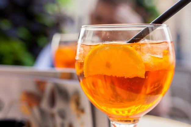 Aperol spritz cocktail. bebida alcoólica à base de mesa com cubos de gelo e laranjas
