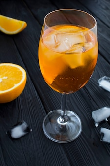 Aperol spritz cocktail em copo de vinho na mesa de madeira preta. fechar-se.