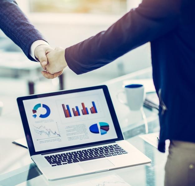 Apertando a mão de parceiros financeiros perto do local de trabalho