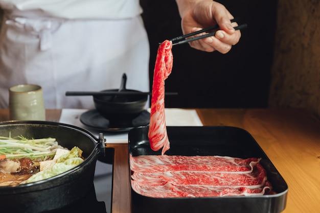 Apertando a mão premium rare slices wagyu carne com textura de alta marmorizada