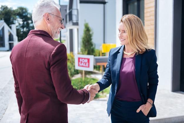 Apertando a mão. próspero homem barbudo de cabelos grisalhos apertando a mão de um corretor de imóveis depois de comprar uma grande casa de luxo