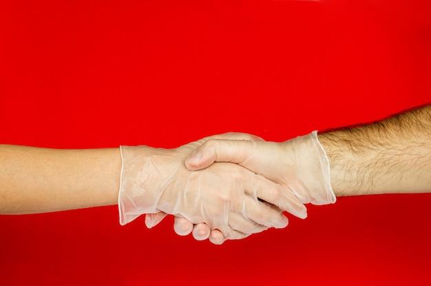 Apertando as mãos de homens e mulheres entregam luvas médicas sobre fundo vermelho. covid-19.coronavirus. proteção contra o vírus.