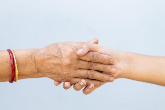 Apertando as mãos em uma parede cinza