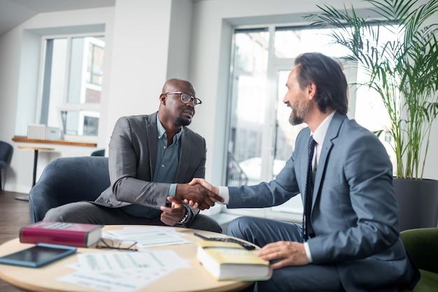 Apertando as mãos. empresário de pele escura apertando a mão de seu economista após consulta no escritório