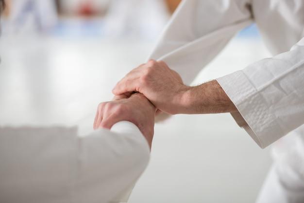 Apertando as mãos. homem praticando aikido apertando a mão de seu rival antes de começar a luta