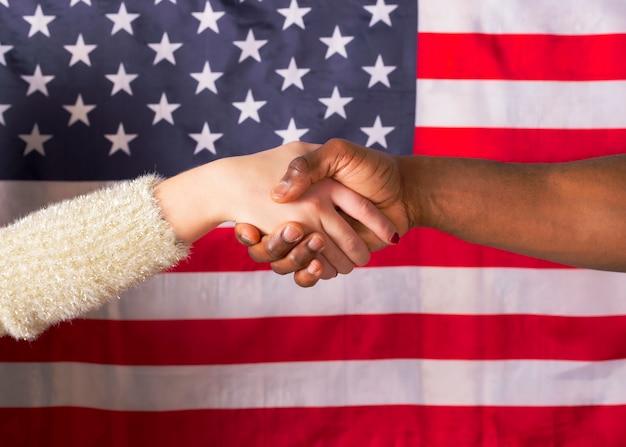 Apertar as mãos e mão branca, interracial, sobre a bandeira americana