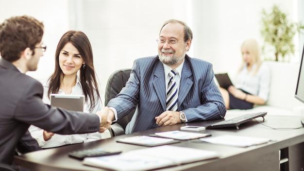 Aperte a mão aos parceiros de negócios após a discussão dos termos financeiros do contrato. a foto tem um espaço vazio para o seu texto