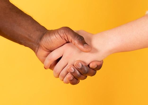 Aperte as mãos e mão branca, interracial,