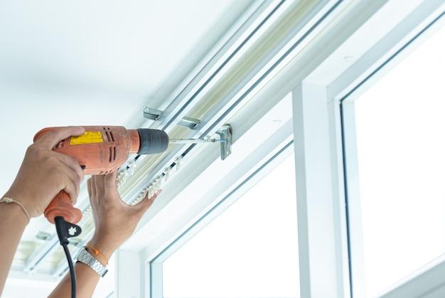 Aperte os parafusos para instalar as cortinas por técnicos profissionais