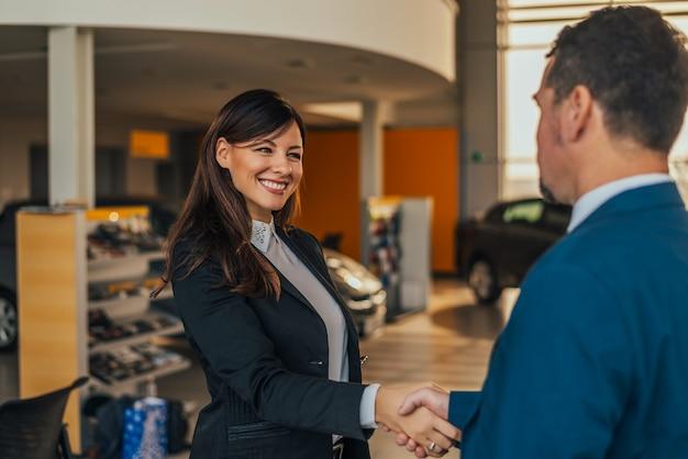 Aperto de mão alegre do negociante de carro com o cliente na sala de exposições.