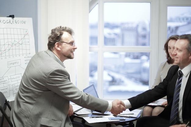 Aperto de mão amigável de parceiros de negócios no escritório. o conceito de parceria