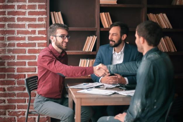 Aperto de mão amigável entre gerente e cliente no escritório criativo.