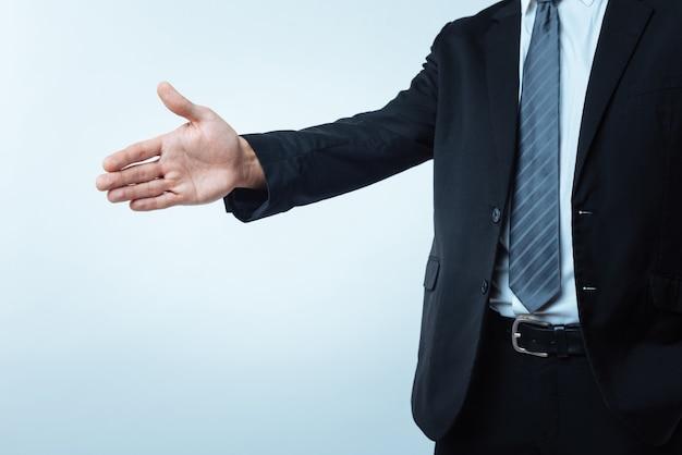 Aperto de mão amigável. perto de uma mão masculina pronta para saudação durante a reunião de negócios