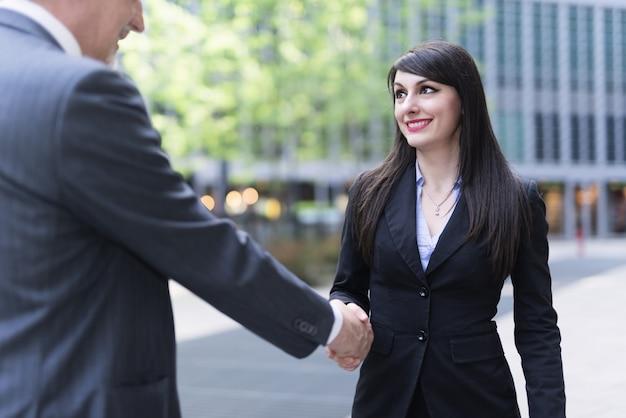 Aperto de mão ao ar livre de pessoas de negócios