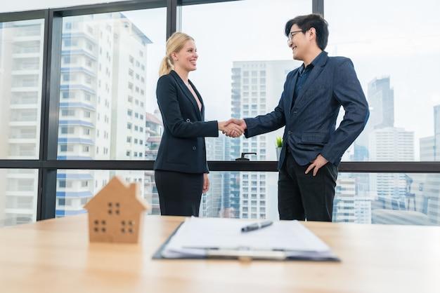 Aperto de mão asiático do homem de negócios com agente imobiliário de propriedade de mulher depois de feito contrato compra de contrato de empréstimo à habitação
