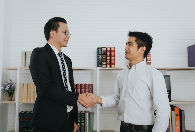 Aperto de mão asiáticos do aperto de mão, terminando acima a reunião, cumprimentando o conceito do negócio.