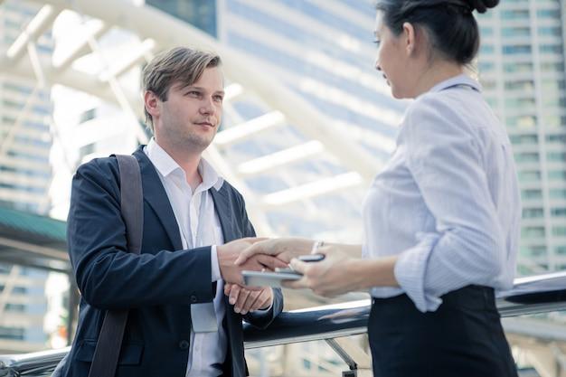 Aperto de mão bem sucedido empresário e empresária depois de um bom negócio.