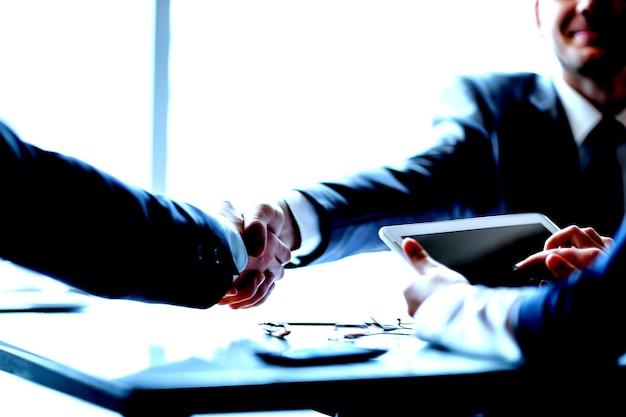 Aperto de mão confiante de executivos no escritório. conceito de parceria